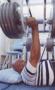 Sri Chinmoy performs a bench press lift